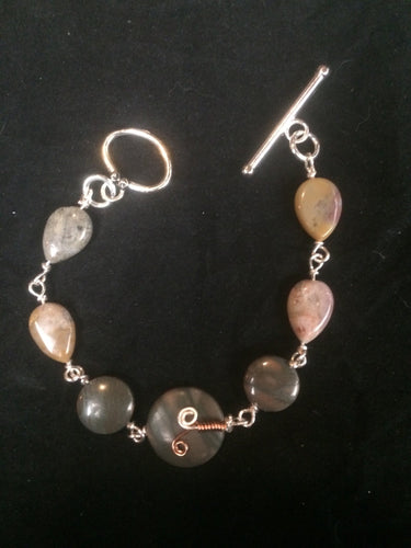 Four 15x10mm teardrop shaped agate beads lead away from two 13mm agate disk beads and an 18mm focal agate bead adorned with a copper sprout wire wrap pattern. A matching silver plated 20x13mm oval toggle clasp completes this 8