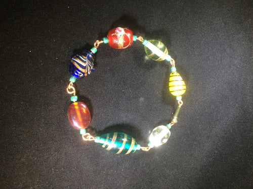 Chunky blown glass beads are linked together with copper wire to form this  8