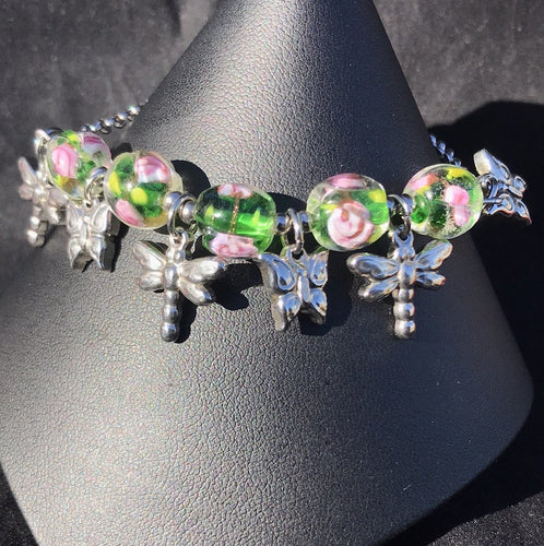 Made from high grade 304 stainless steel, this sturdy corrosion-resistant bracelet features blown glass beads depicting flowers, accented by stainless steel dragonfly charms between the beads.