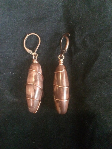 A pair of 30x10mm cavatelli-shaped agate beads is wrapped in copper wire in a spiral pattern, then set onto copper plated brass leverbacks. These earrings are designed to be a matching set with necklace (Spiral Cavatelli Copper Wire Wrapped Agate Necklace - SKU 1NCK0010)
