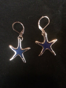 A pair of silver plated sea star beads that change color with temperature sits below silver plated brass leverbacks.