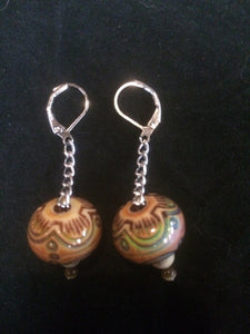 A pair of drum shaped mood beads that change color with temperature sit on a silver plated chain below silver plated brass leverbacks.