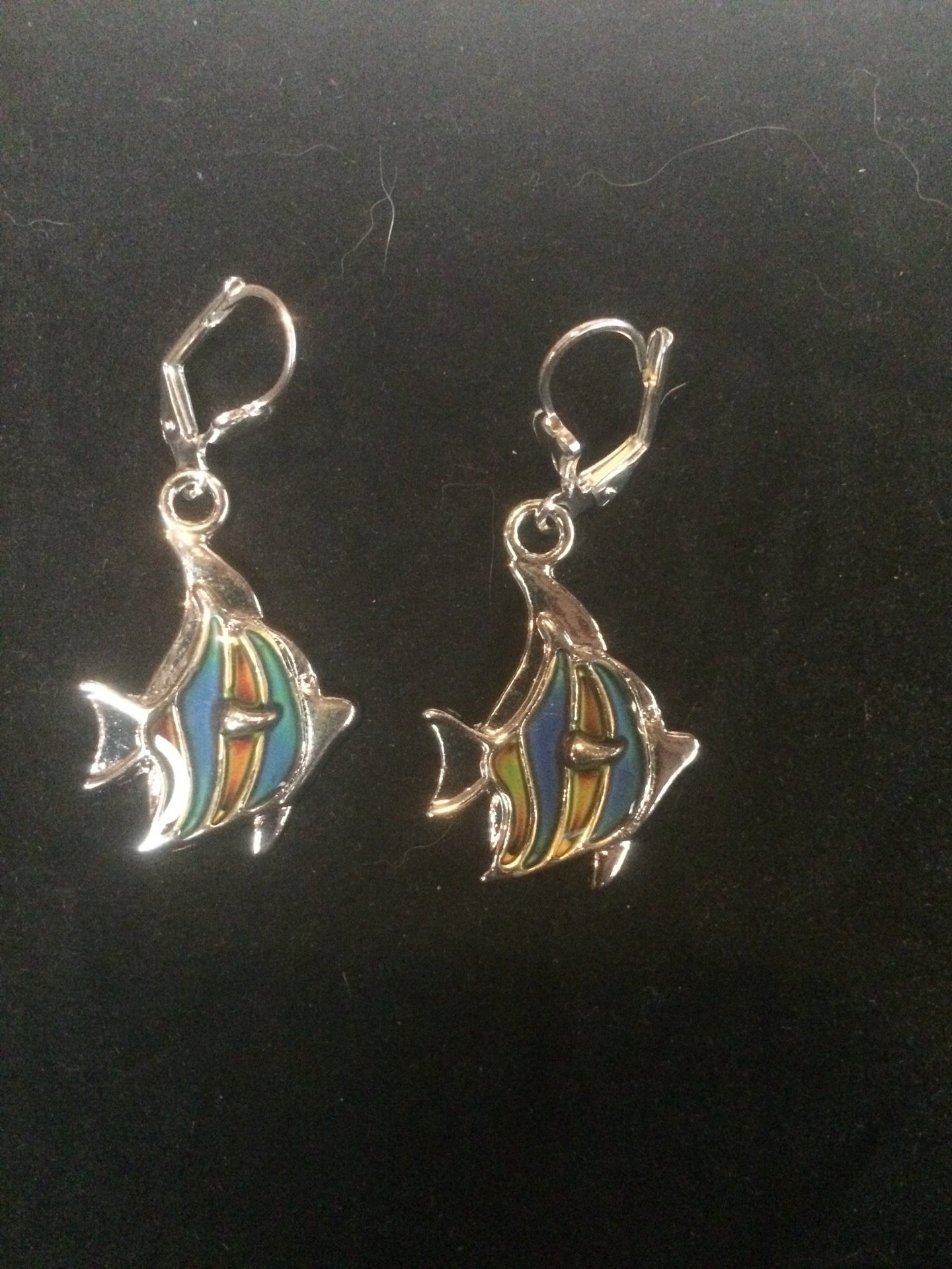 A pair of silver plated fish beads that change color with temperature sits below silver plated brass leverbacks.