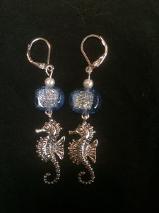 A pair of 10mm dichroic glass beads accent silver plated pewter seahorse charms below silver plated brass leverbacks.