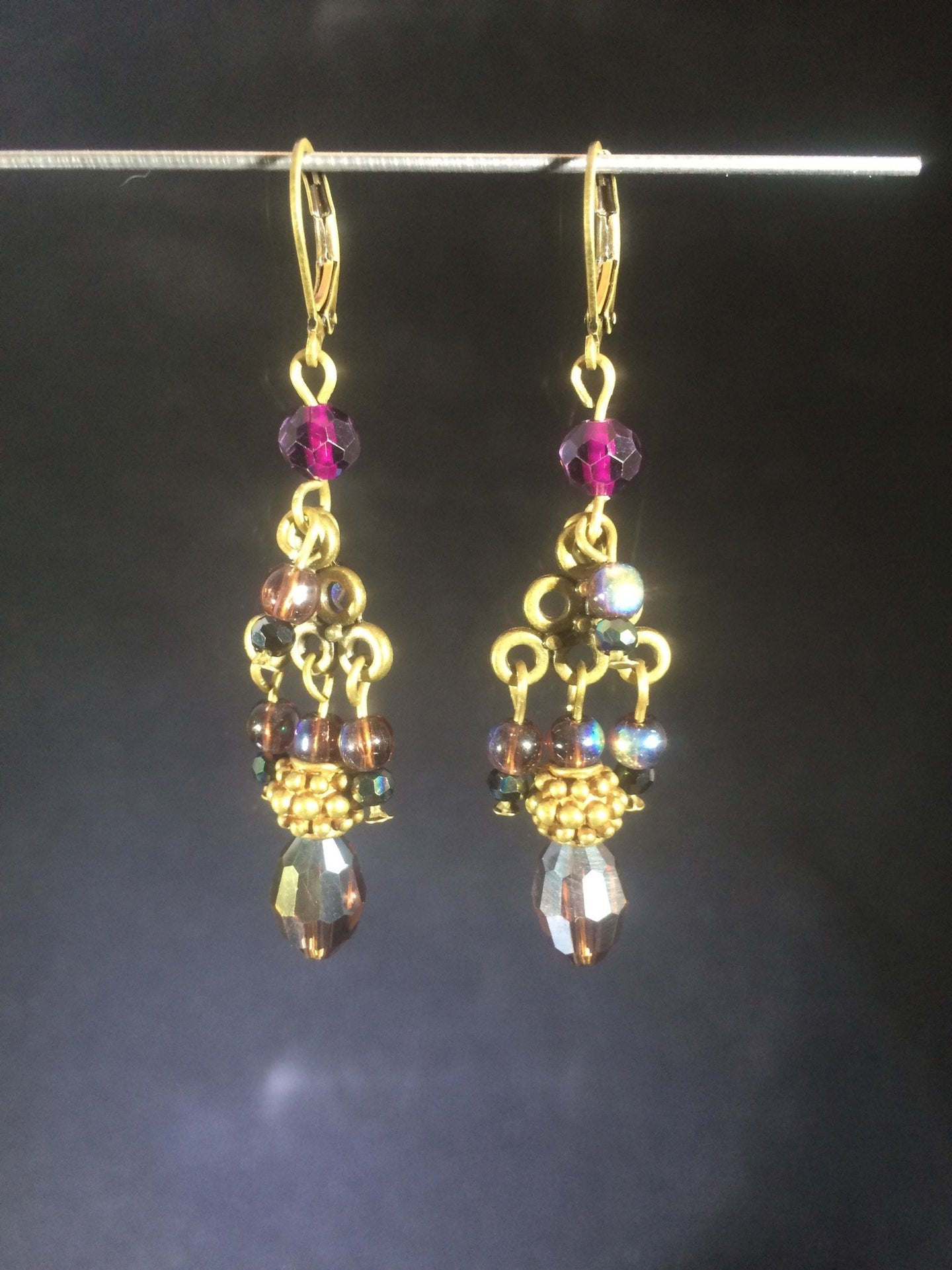 This pair of layered chandelier leverbackåÊearrings is made with a mixture of metal beads, glass peals, and faceted Czech crystal beads, set on plated zinc pewter chandeliers.
