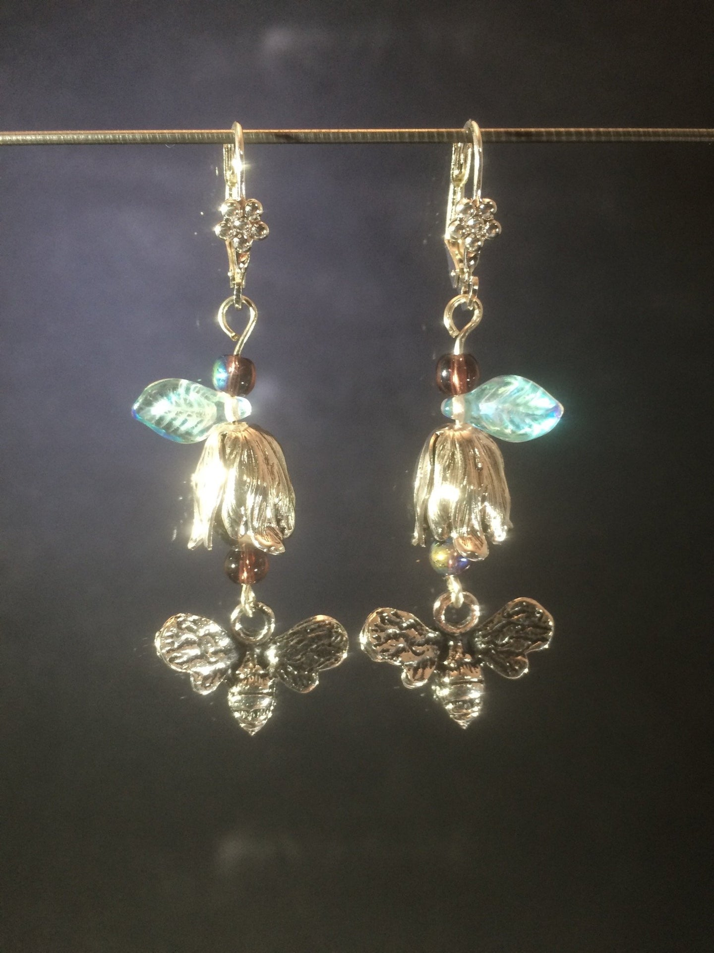 These leverback earrings feature silver plated zinc petwer charms of bees and flowers along with Czech pressed glass leaves and glass pearls.
