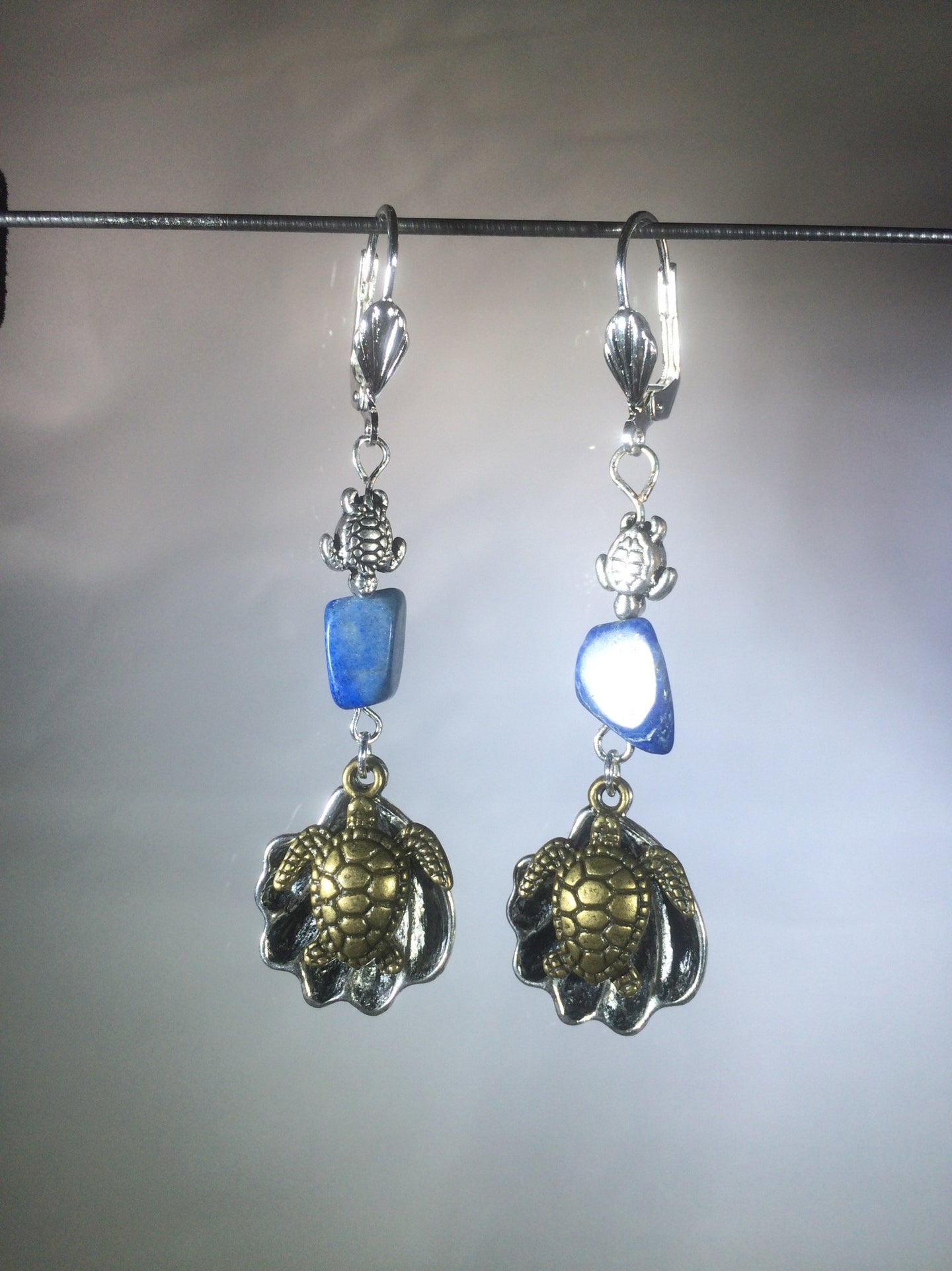 Leverback earrings made from plated metal charms and findings with an 8mm lapis lazuli bead to add a vibrant blue color.