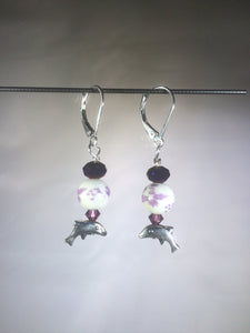 Leverback earrings with a metal leaping dolphin charm and Swarovski crystal beads.