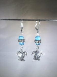 Leverback earrings with metal sea turtle charms, blue colored and faceted glass beads, and a faceted crystal cluster.