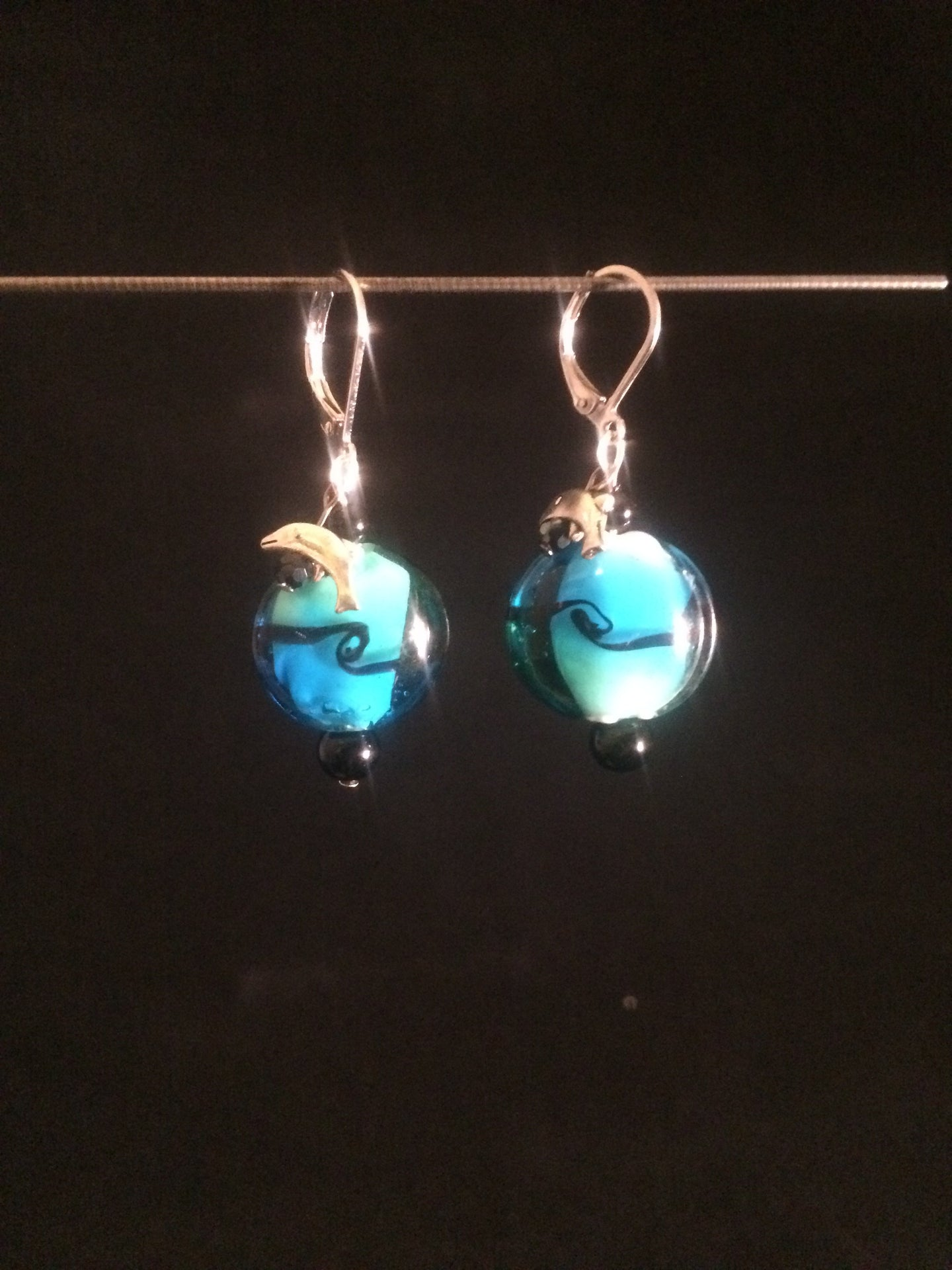 Leverback earrings made with a blue blown glass bead and adorned with a plated metal charm of either a fish, dolphin, or a shell.  Faceted and round glass beads are added for accent.