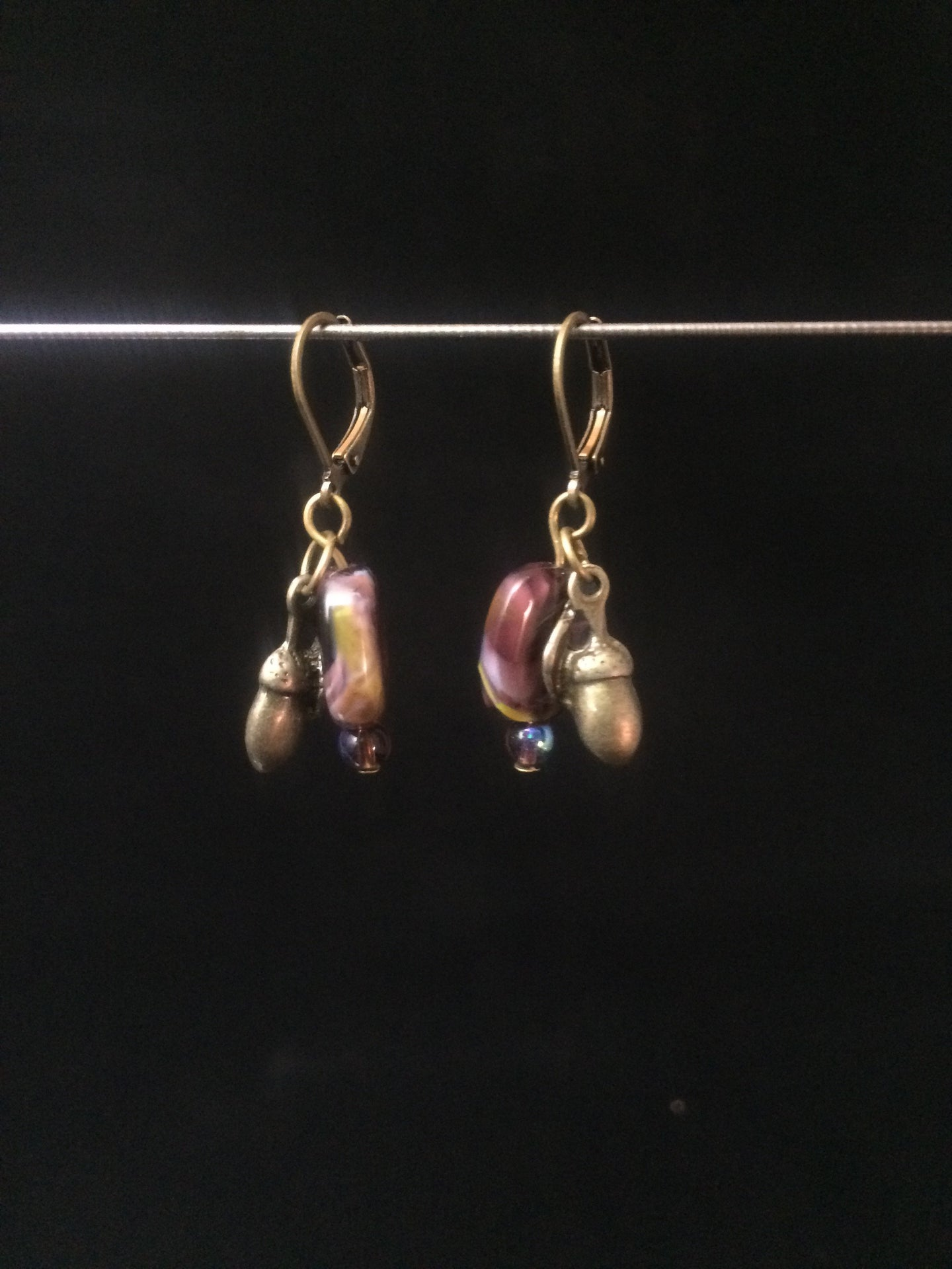 Leverback Earrings made from purple blown glass beads that have swirls and metal acorn charms.åÊ Round glass pearls are added for accent.