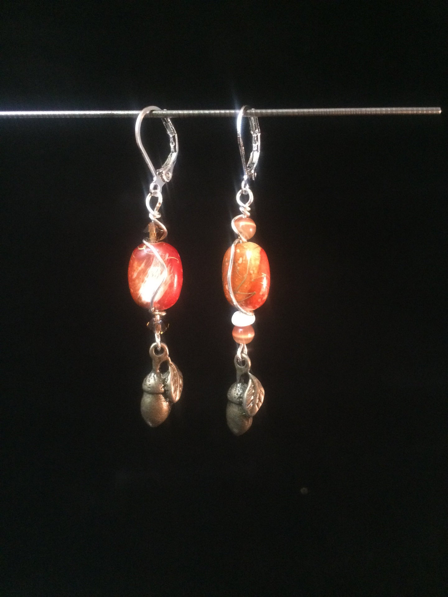 Leverback earrings made from glass beads and metal acorn charms.
