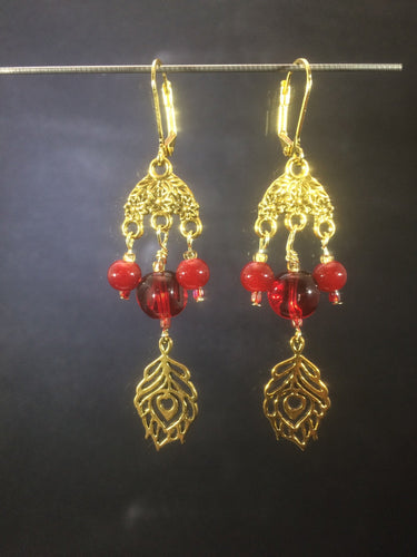 Leverback chandelier earrings adorned with red glass beads and a metal feather charm.