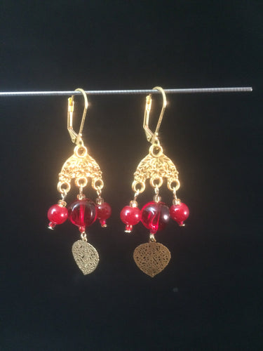 Leverback chandelier earrings adorned with red glass beads and a metal leaf charm.