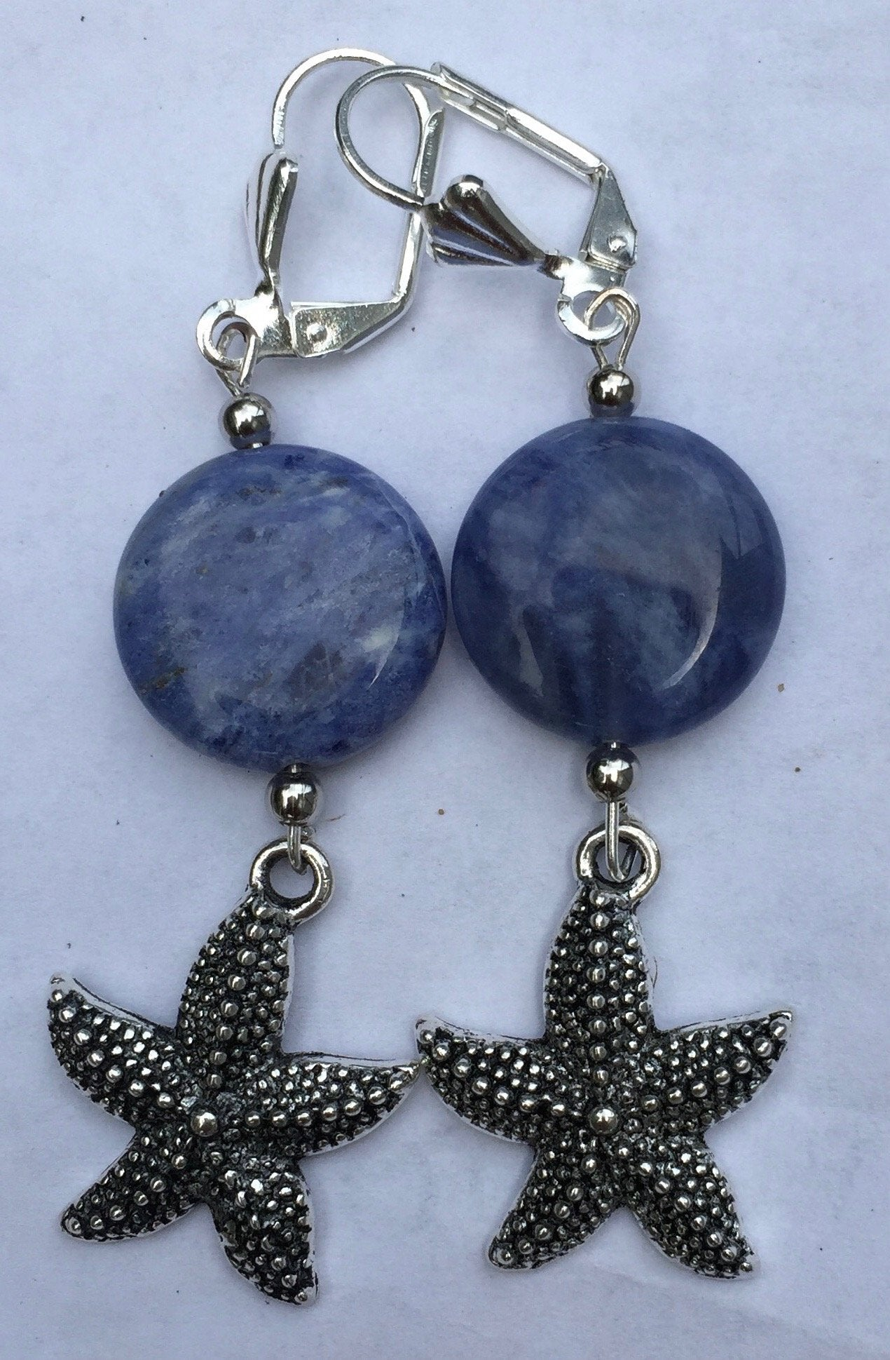 Sodalite beads and scallop charms dangle below silver plated leverbacks. Variations: Scallop, Starfish, Conch.