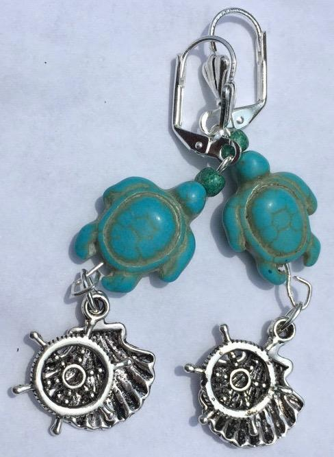 Dyed magnesite beads carved into the shape of sea turtles form the focus of these silver plated brass leverback earrings. Metal oyster and wheel charms complete the look.