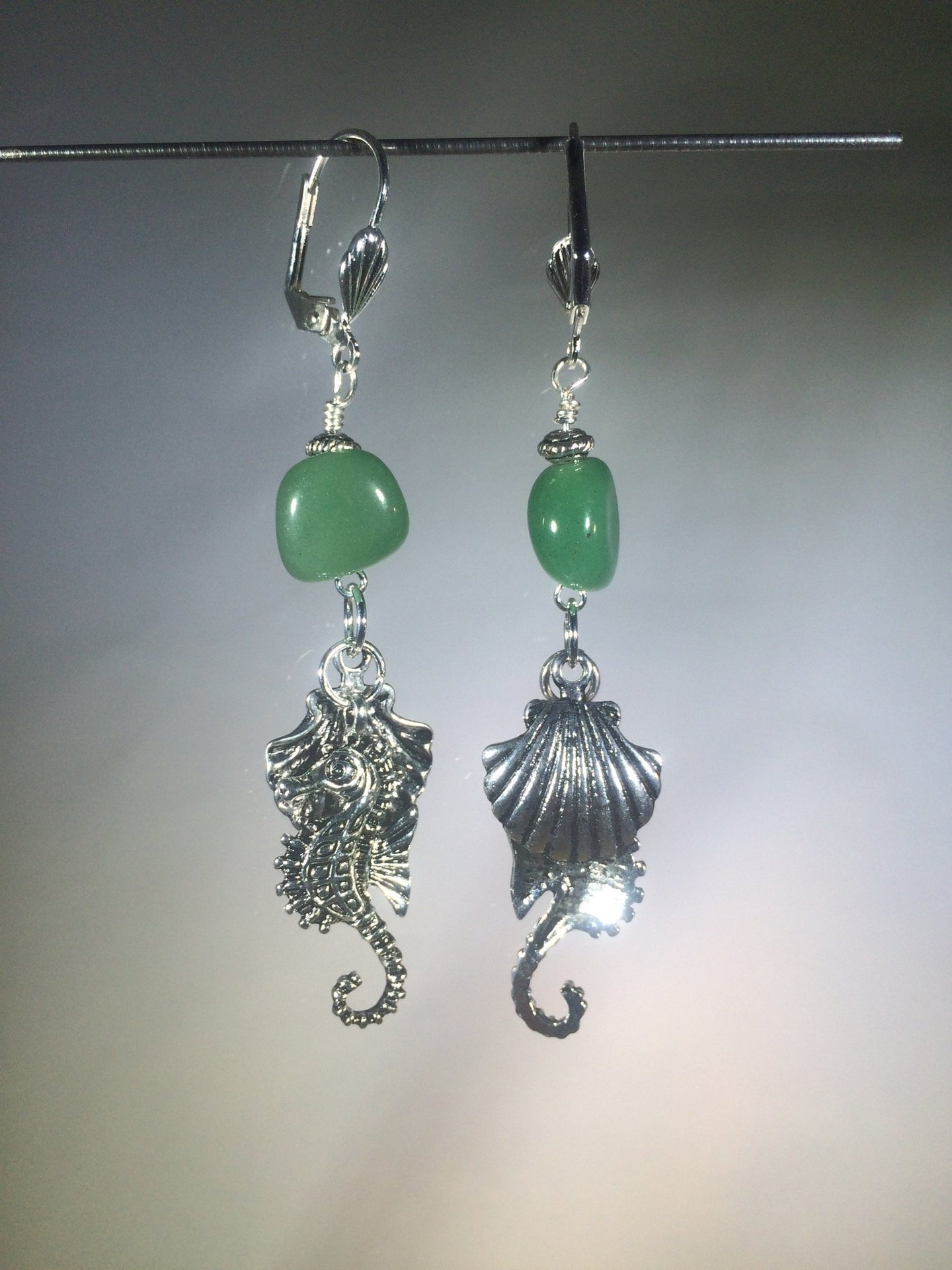 Metal seahorse and scallop shell charms tinkle together as they dangle below a 10mm asymmetric green aventurine bead, all mounted on silver plated brass leverbacks. Variations: (A) Seahorse, (B) Sea Turtle