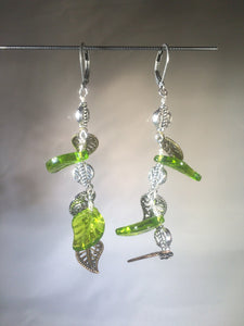 "A mixture of vivid green Czech pressed glass leaves and metal leaf charms and beads dangle to the side on these 2"" drop jointed silver plated brass leverback earrings."