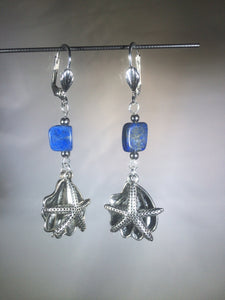 Metal sea star (starfish) and oyster charms dangle below a vibrant blue 8mm lapis lazuli bead in these silver plated brass leverback earrings.