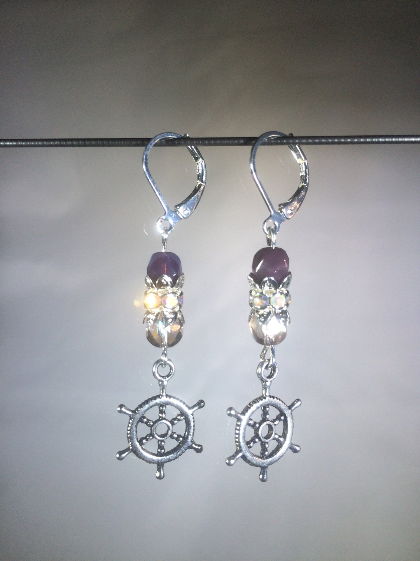 Leverback earrings with metal ship's wheel charms, purple colored and faceted glass beads, and a faceted crystal cluster.