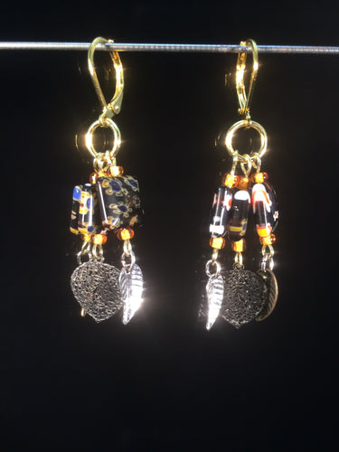 These chandelier-styleåÊleverbackåÊearrings featureåÊ10mm square black millefiore beads with shiny leaf charms dangling below, for a total dangle length of about 1.5