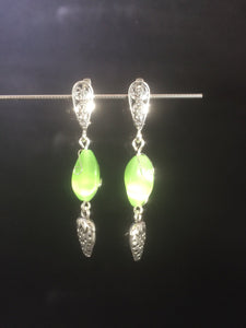 "Tiny metal strawberry charms dangle from chatoyant green glass beads below silver plated brass leverbacks in these 1.5"" drop earrings. These form a matching set with necklace 1NCK0103."