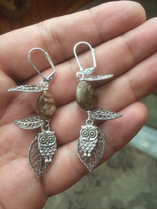 These earrings feature a metal owl dangling below falling metal leaves. This forms a matching set with necklace 1NCK0029.