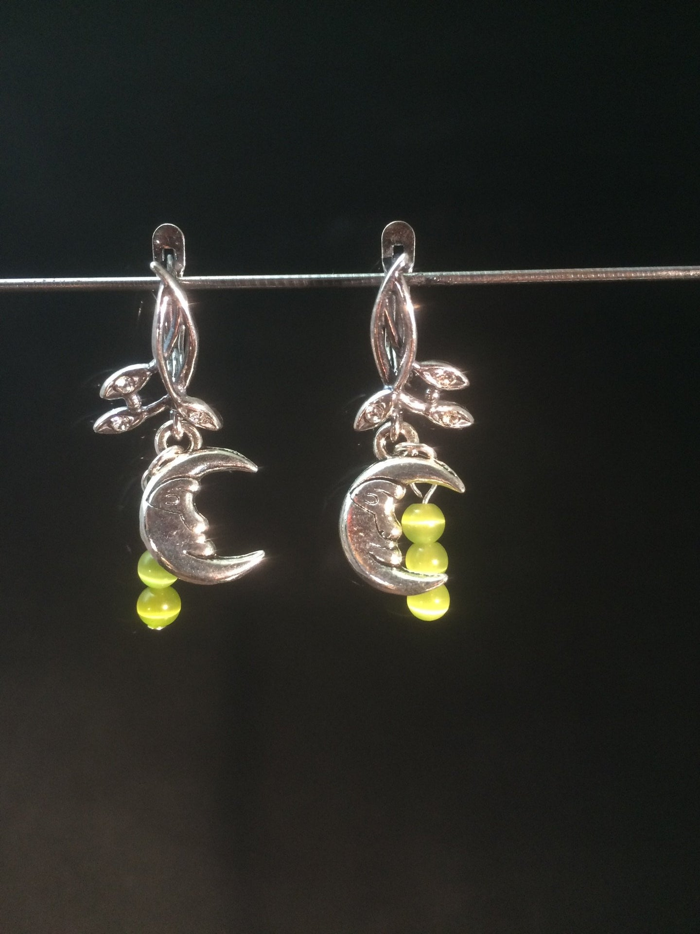 A silver plated moon charm is adorned with natural peridot beads, then set on silver plated brass leverbacks. These earrings form a matching set with necklace 1NCK0053.