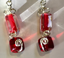 Load image into Gallery viewer, Red glass beads form geometric patterns in rectangles and cylinders, with swirly silver wire looped in between on these leverback silver earrings.