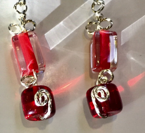 Red glass beads form geometric patterns in rectangles and cylinders, with swirly silver wire looped in between on these leverback silver earrings.