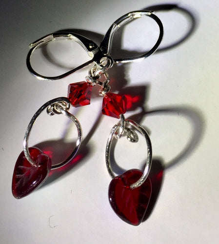 Delicate fine silver loops hold dangling irridescent red glass heart shaped leaf beads below a shiny red Swarovski bicone in these silver leverback earrings. The backs of the glass leaves are irridescent blue, giving them extra shimmer as they rustle with your movement!
