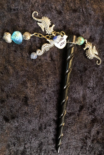 SEAHORSIES!! A six inch wooden hairstick is adorned with silver plated pewter seahorse charms, Czech pressed glass, and dyed shell beads mounted on a silver plated chain. A Swarovski chaton adorns the tip.