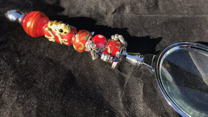 Blown glass beads featuring a raised frog peek out among leafy and flowery charms on the handle of this magnifying glass.
