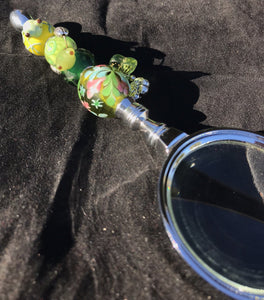 A blown glass bead depicting a tiny frog face peeking out from underwater caps off the sunlit garden imagery on the handle of this magnifying glass.