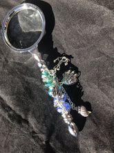 Load image into Gallery viewer, An anchor charm fixes the location conjured up by the sea life charms and dazzling blue-green cut and blown glass beads on the handle of this magnifying glass.