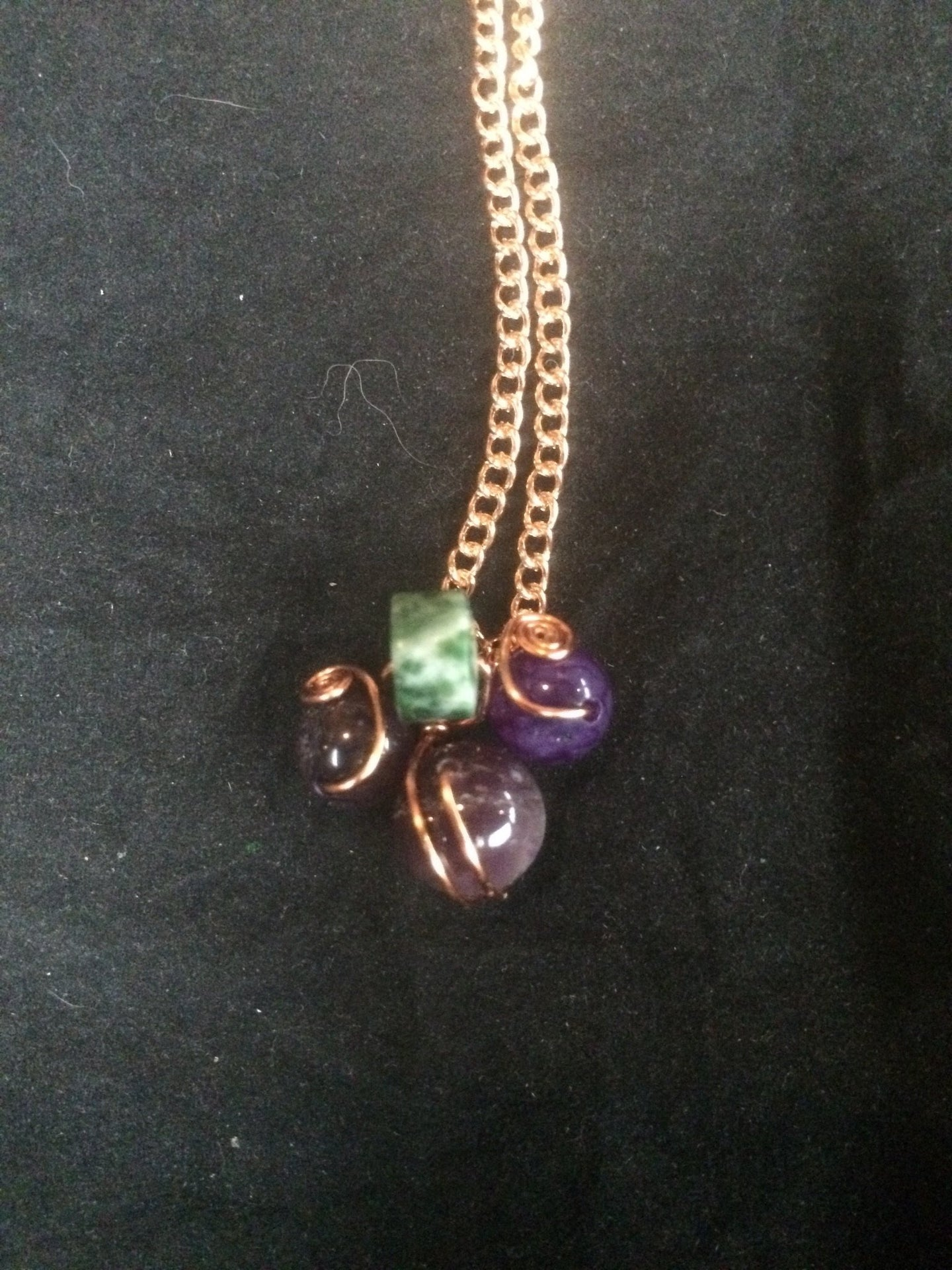 Three amethyst beads surround a green and white agate bead in a design meant to be evocative of a cluster of grapes, with the swirling copper wire wrap evoking images of the vine. The pendant is set on a 22