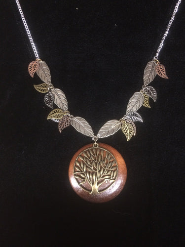 In this necklace, a wooden disk backs aåÊmetal tree of life pendant with metal leaves of different finishes and sizes surrounding it on the 18