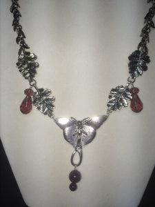 A necklace made from plated metal charms, faceted glass beads, and round glass pearls.