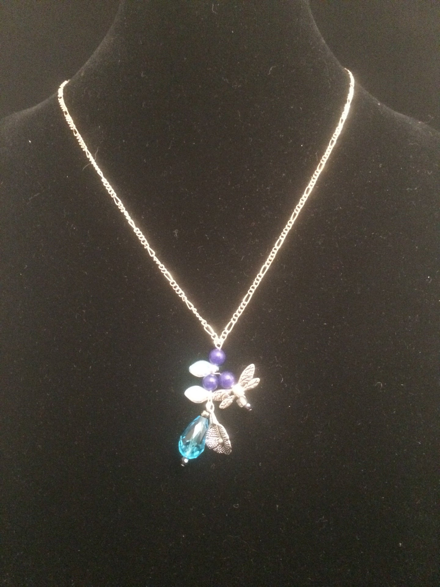 Necklace set with a lily theme accented with blue glass beads and blue faceted beads and metal charms. Forms a matching set when purchased with earrings 1EAR0136.