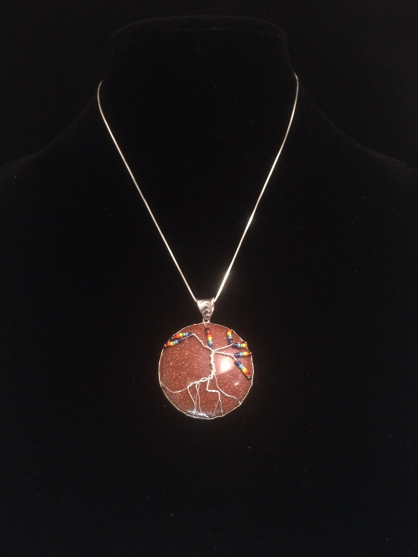 This tree of life uses the inclusive rainbow as the color theme made with glass seed beads on fine silver wire on a silver chain. The background is a 30mm cabochon of lab created sunstone in gold.