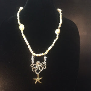 This shell necklace features a metal octopus holding a sea star dangling from the tails of two metal seahorses. The bracelet has a smaller octopus charm and a sanddollar charm.