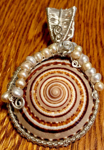 "A 2"" diameter cone snail shell is wrapped in woven fine silver and accented with freshwater cultured pearls to form this pendant. The pendant is mounted on a 16"" sterling silver chain, so that the shell sits right at the collarbone. The wire weave extends to the back of the shell, ensconcing the shell's opening--you can see right down into the shell's interior!"