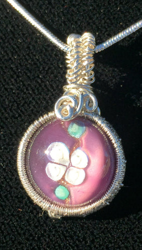 A purple 14mm blown glass cabochon depicting an apple blossom is woven into a fine silver pendant, then set on a 20