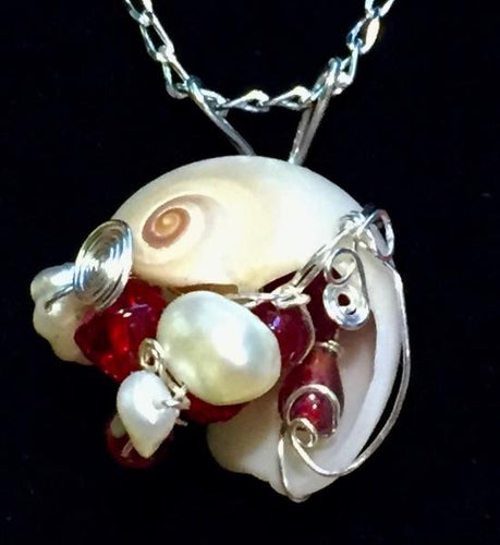 Glass beads and freshwater pearls dazzle amongst fine silver wire swirls passing into and through an ethically beachcombed shell found on St. Augustine Beach, FL. The pendant is set onto a 16