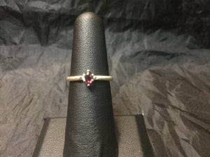 A 5x3mm natural rhodolite gemstone is set into a beefy USA-made sterling silver ring mounting. This ring is approximately a size 6.