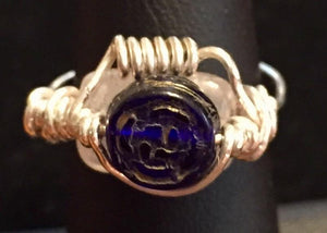 A natural 10x8mm cherry quartz bead is wrapped behind an embossed blue glass bead with fine silver wire coils in this fanciful ring. Rings made by this wire wrapping method vary individually. This one is approxmately a size 4.75, but may fit a slightly larger finger depending on how snug a fit you prefer.