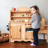 Little girl baking Wooden toy kitchen