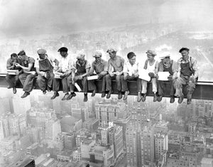 Black and white historical photo of iron workers eating lunch on a construction beam suspended above NYC.