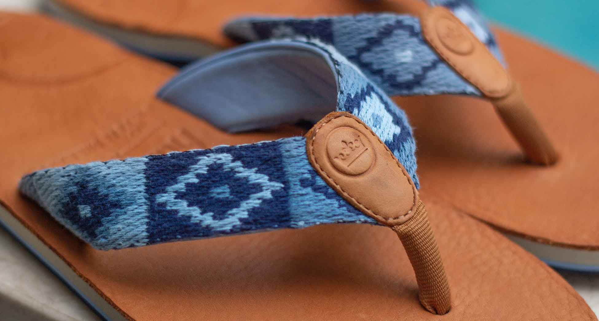 a close up shot of HM x Peter Millar flip flops with vegetable-tanned leather soles, blue woven straps with memory foam in the toe post and straps