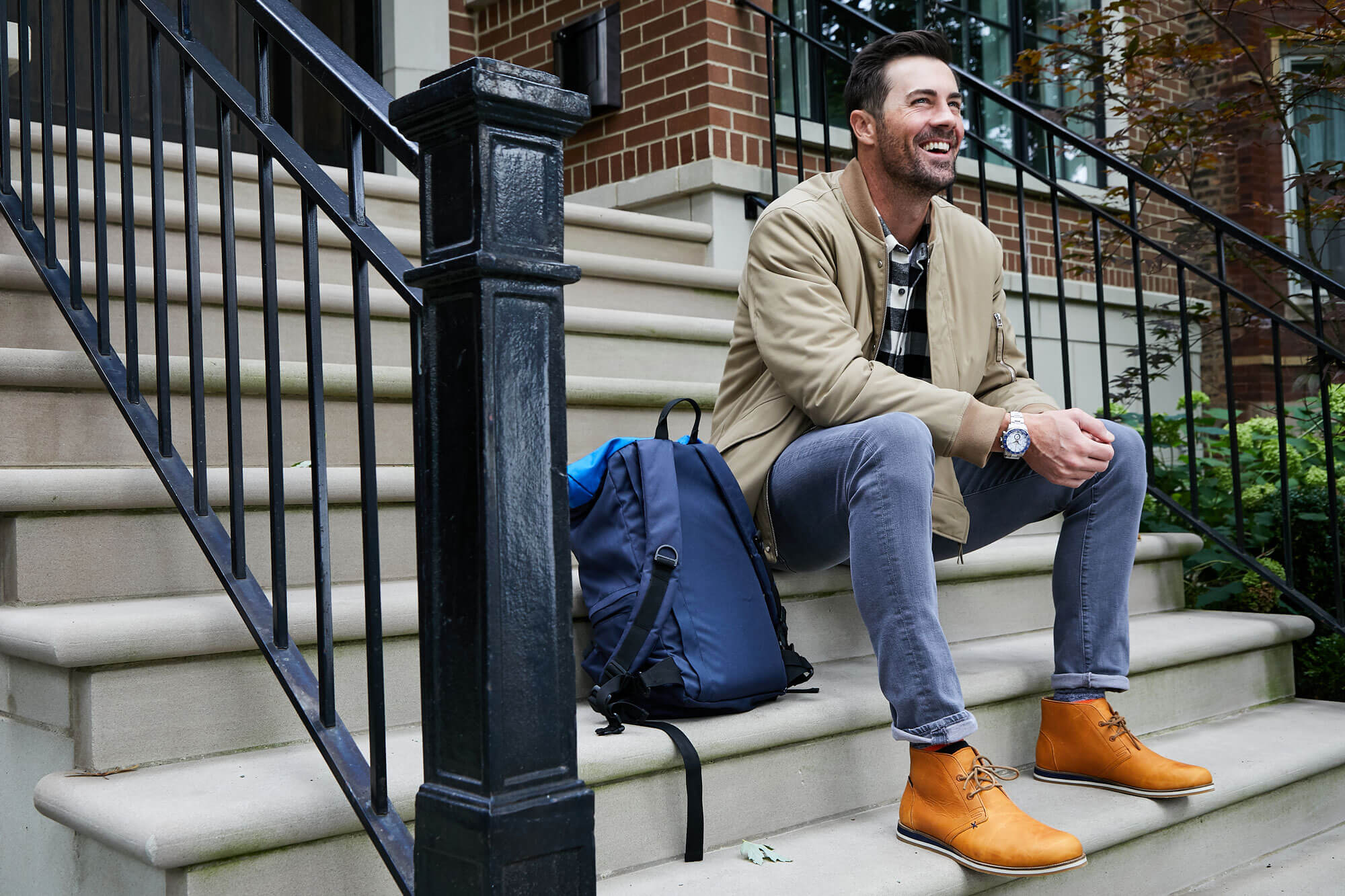 Cole Hamels sits on a stoop in Chicago, Illinois wearing blue chinos, a buffalo checkered shirt, tan jacket, blue backpack, and Rye HM x Nokona Adobe Desert Boots. He's smiling at someone standing in front of him, out of frame.